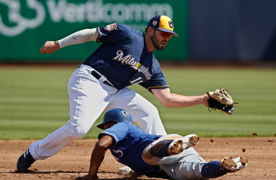 Texas' Danny Santana slides safely into second base under the tag of Brewers second baseman Mike Moustakas during a pick-off attempt March 19.