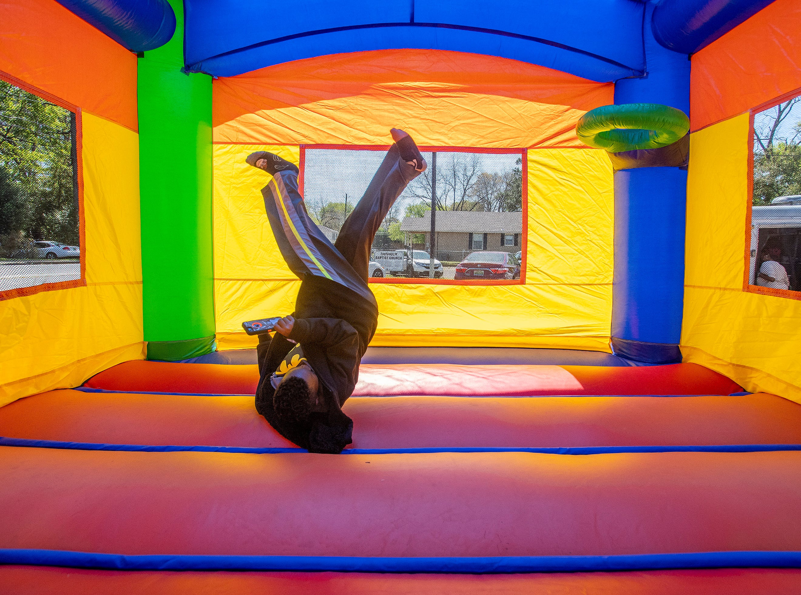 Children jump in a bounce house as Flatline Church hosts a block party for the Chisholm neighborhood in Montgomery, Ala., on Saturday March 23, 2019.