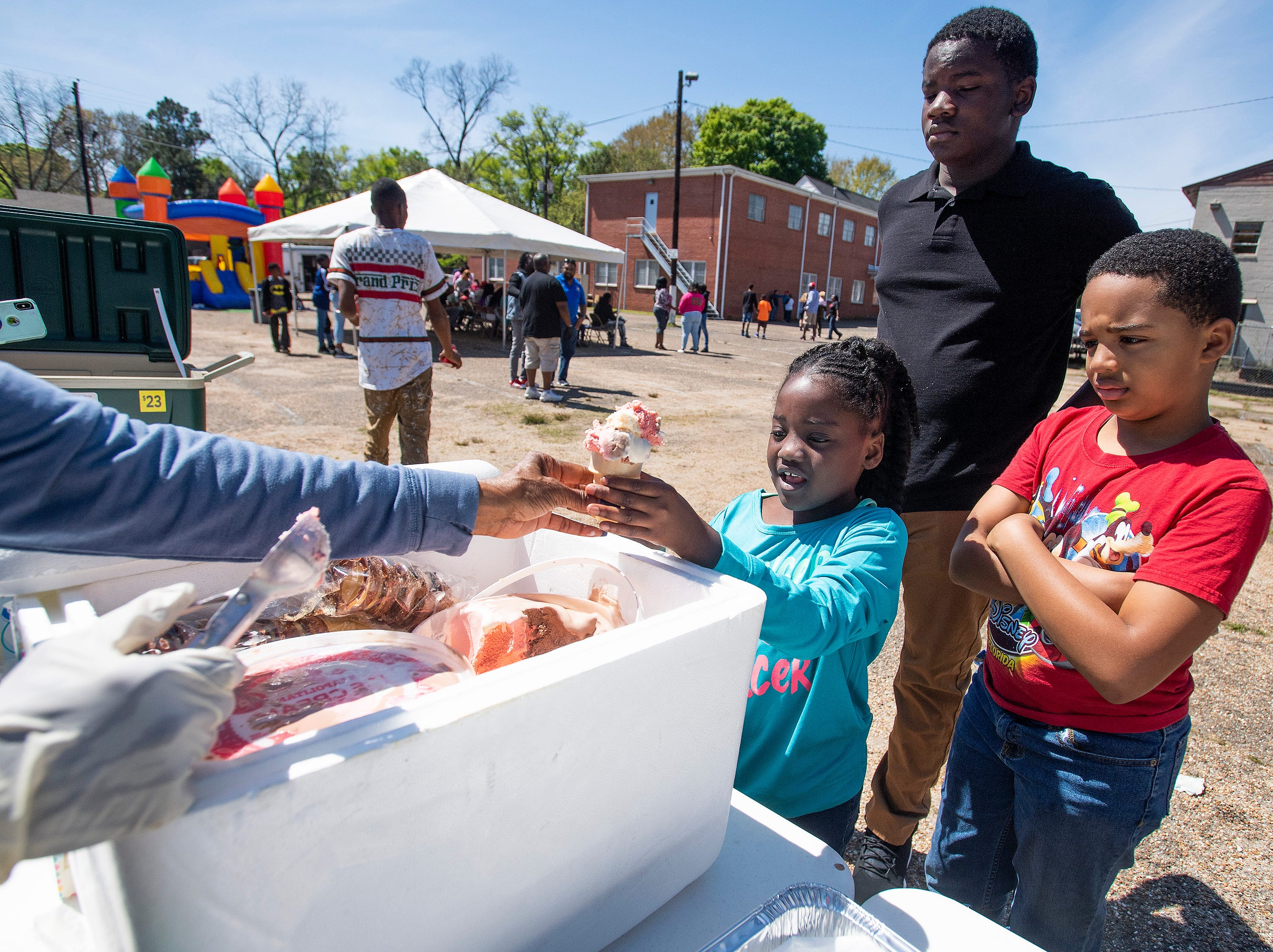 Ice cream is served as Flatline Church hosts a block party for the Chisholm neighborhood in Montgomery, Ala., on Saturday March 23, 2019.
