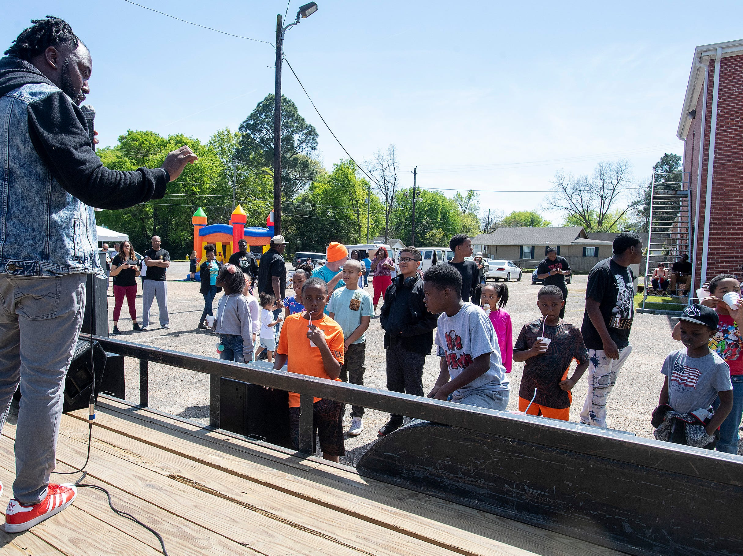 Pastor DeWayne Rembert speaks as Flatline Church hosts a block party for the Chisholm neighborhood in Montgomery, Ala., on Saturday March 23, 2019.