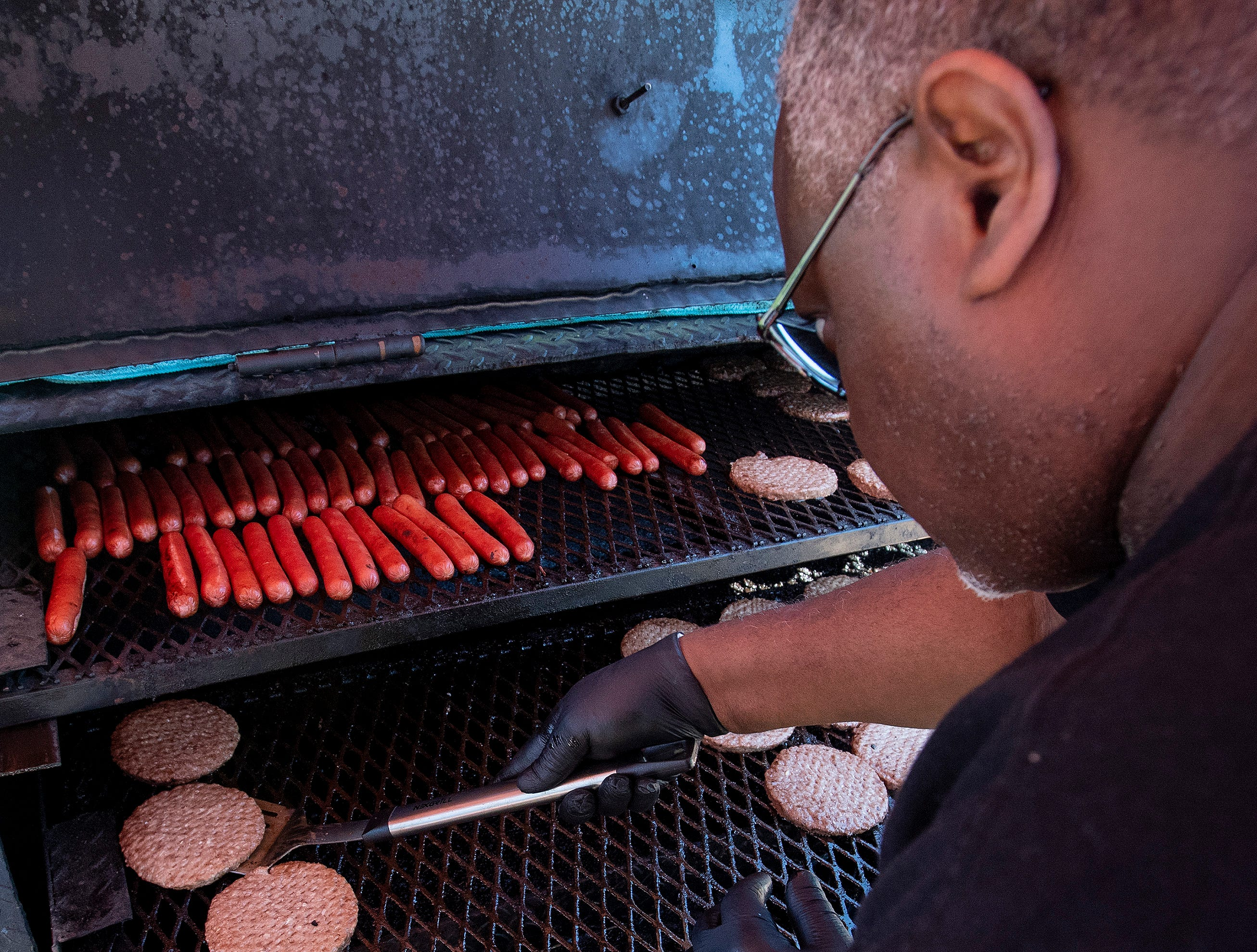 Burgers and hot dogs are prepared as Flatline Church hosts a block party for the Chisholm neighborhood in Montgomery, Ala., on Saturday March 23, 2019.