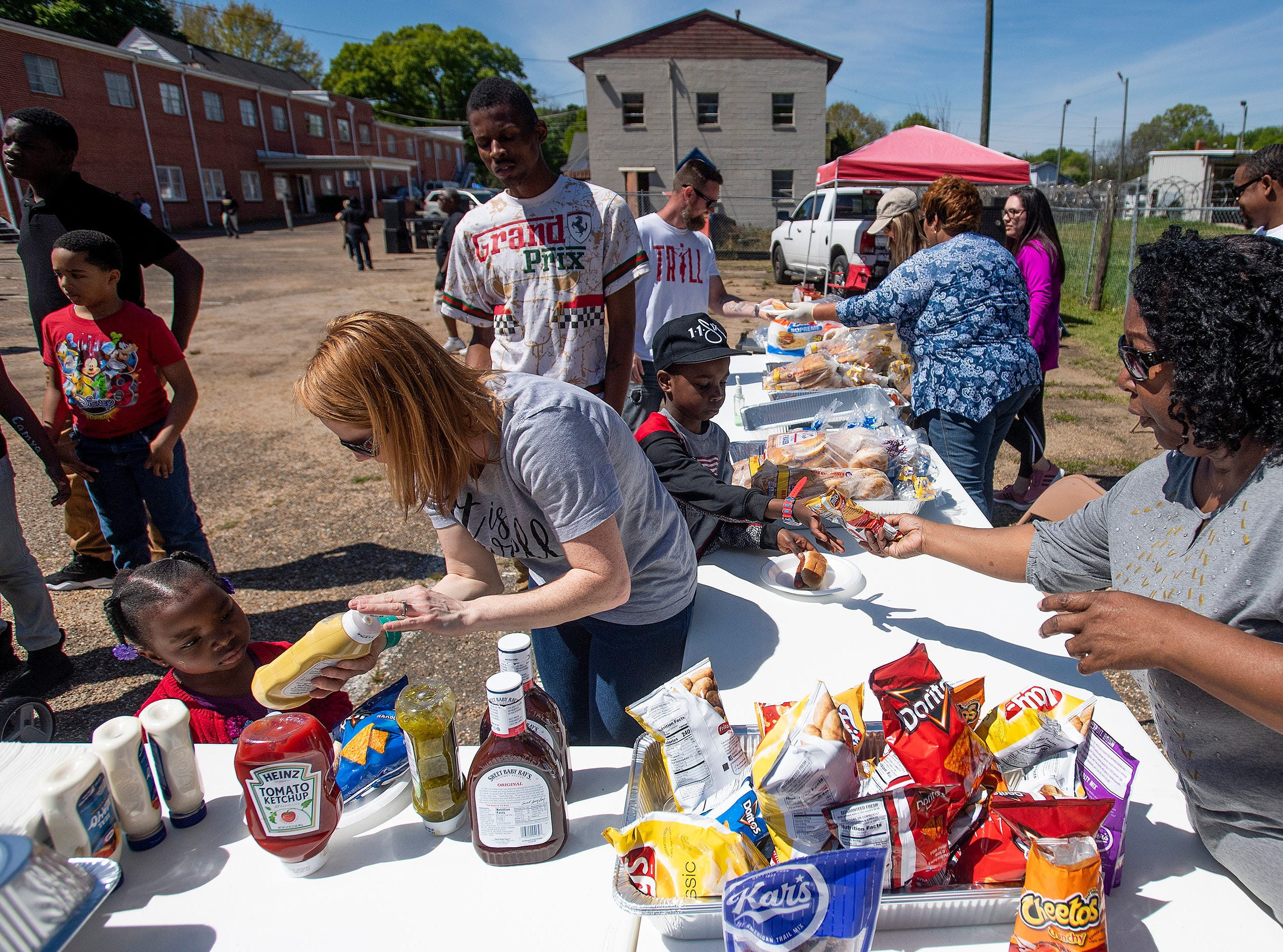 Hamburgers and hotdogs are served as Flatline Church hosts a block party for the Chisholm neighborhood in Montgomery, Ala., on Saturday March 23, 2019.