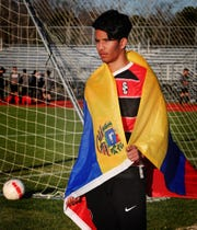 Stewarts Creek soccer player Nerio Flores, who immigrated from Venezuela, is draped in his homeland's flag prior to Friday's match against Oakland.