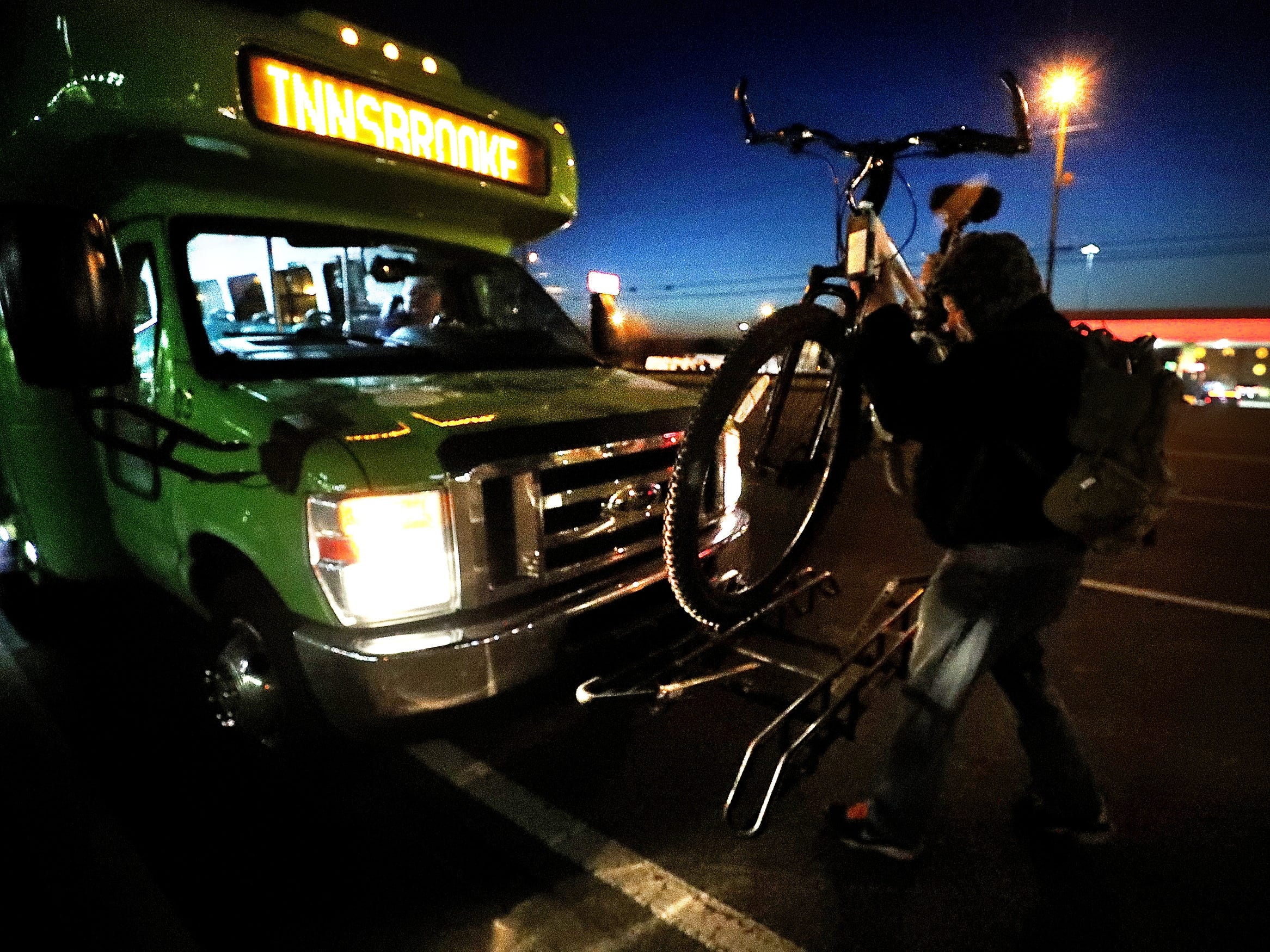Daniel Zienkiewicz removes his bike from the front of the Rover bus at his stop on South Church Street before he continues to cross seven lanes of traffic and ride for 2 more miles before arriving at his job. Zienkiewicz was told by passengers on this morning commute that a pedestrian had been hit and killed crossing this highway the night before.