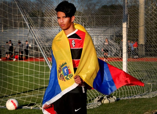 Nerio Flores, a Stewarts Creek soccer player originally from Venezuela is wrapped in his countries flag on Friday, March 22, 2019, in Smyrna.