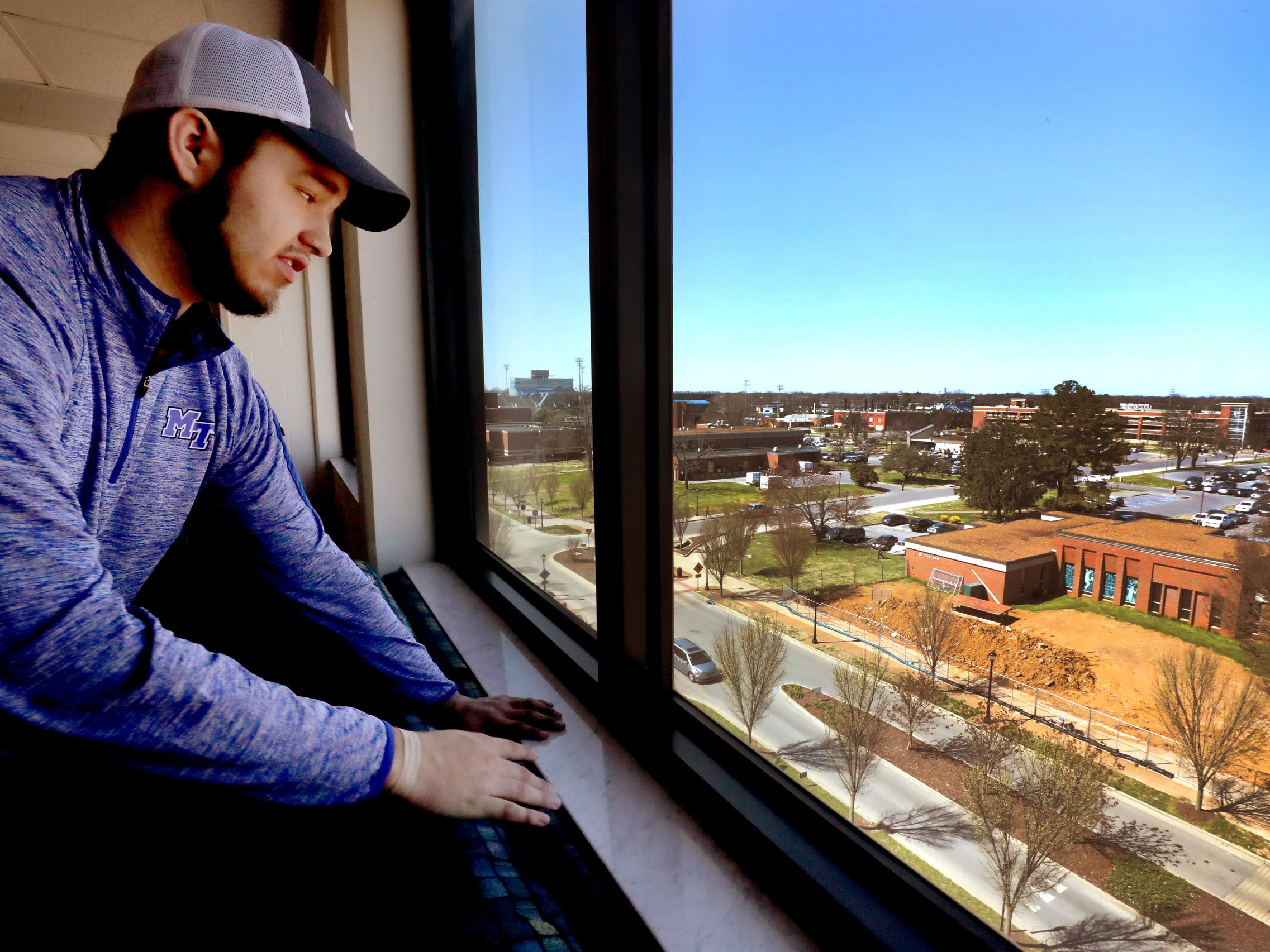Isaac Plata looks over some of MTSU's campus from the common area on his floor at Jim Cummings Hall, on Friday, March 22, 2019.