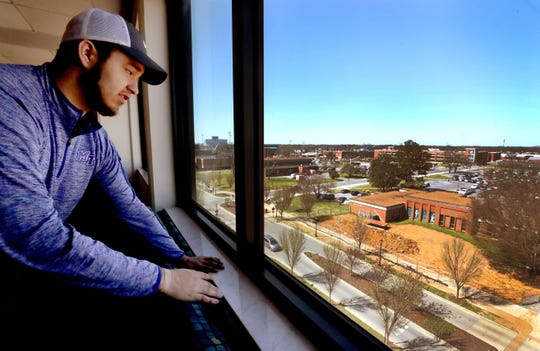 Isaac Plata looks over some of MTSU's campus from the common area on his floor at Jim Cummings Hall on March 22.