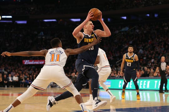 Mar 22, 2019; New York, NY, USA; Denver Nuggets center Nikola Jokic (15) drives past New York Knicks point guard Frank Ntilikina (11) during the first quarter at Madison Square Garden.