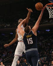 Mar 22, 2019; New York, NY, USA; Denver Nuggets center Nikola Jokic (15) is fouled by New York Knicks center Mitchell Robinson (26) as he shoots during the first quarter at Madison Square Garden.