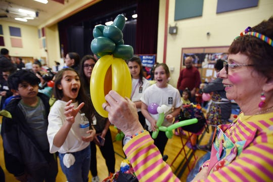 Dolly the Clown, (Dolly Pagano) makes a balloon pineapple as Anjali (age 12) reacts as she receives it during the 3rd annual March Madness Food & Fun Day to benefit the Rutherford Food Pantry hosted by the Rutherford Education Association at Washington School in Rutherford on 03/23/2019.