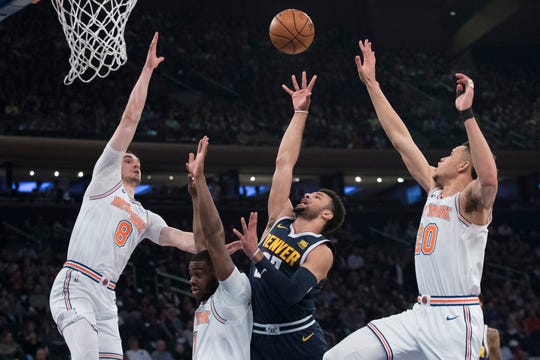Denver Nuggets guard Jamal Murray,second from right, goes to the basket against New York Knicks forward Mario Hezonja (8), guard Emmanuel Mudiay (1) and forward Kevin Knox (20) during the first half of an NBA basketball game, Friday, March 22, 2019, at Madison Square Garden in New York.