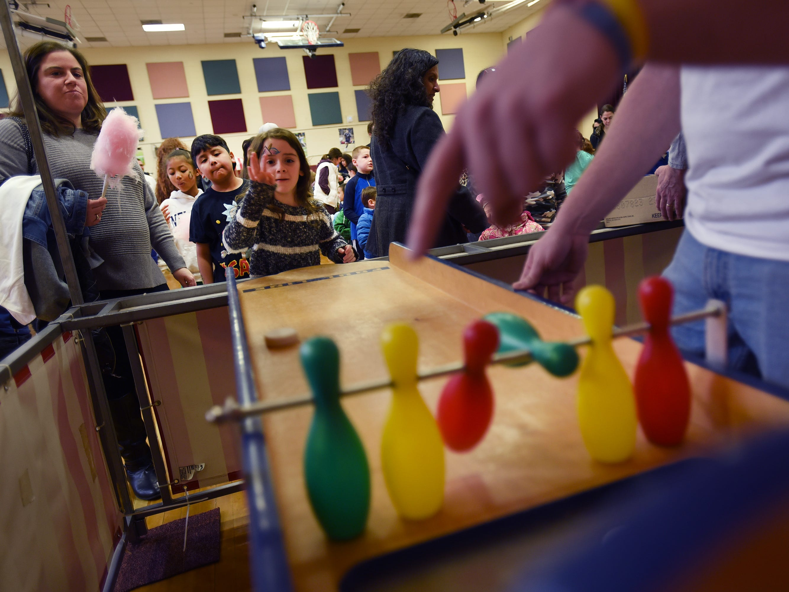 Avery Ben-Ami (age 8) of Rutherford, plays table bowling as her mother Bree (L) looks on during the 3rd annual March Madness Food & Fun Day to benefit the Rutherford Food Pantry hosted by the Rutherford Education Association at Washington School in Rutherford on 03/23/2019.