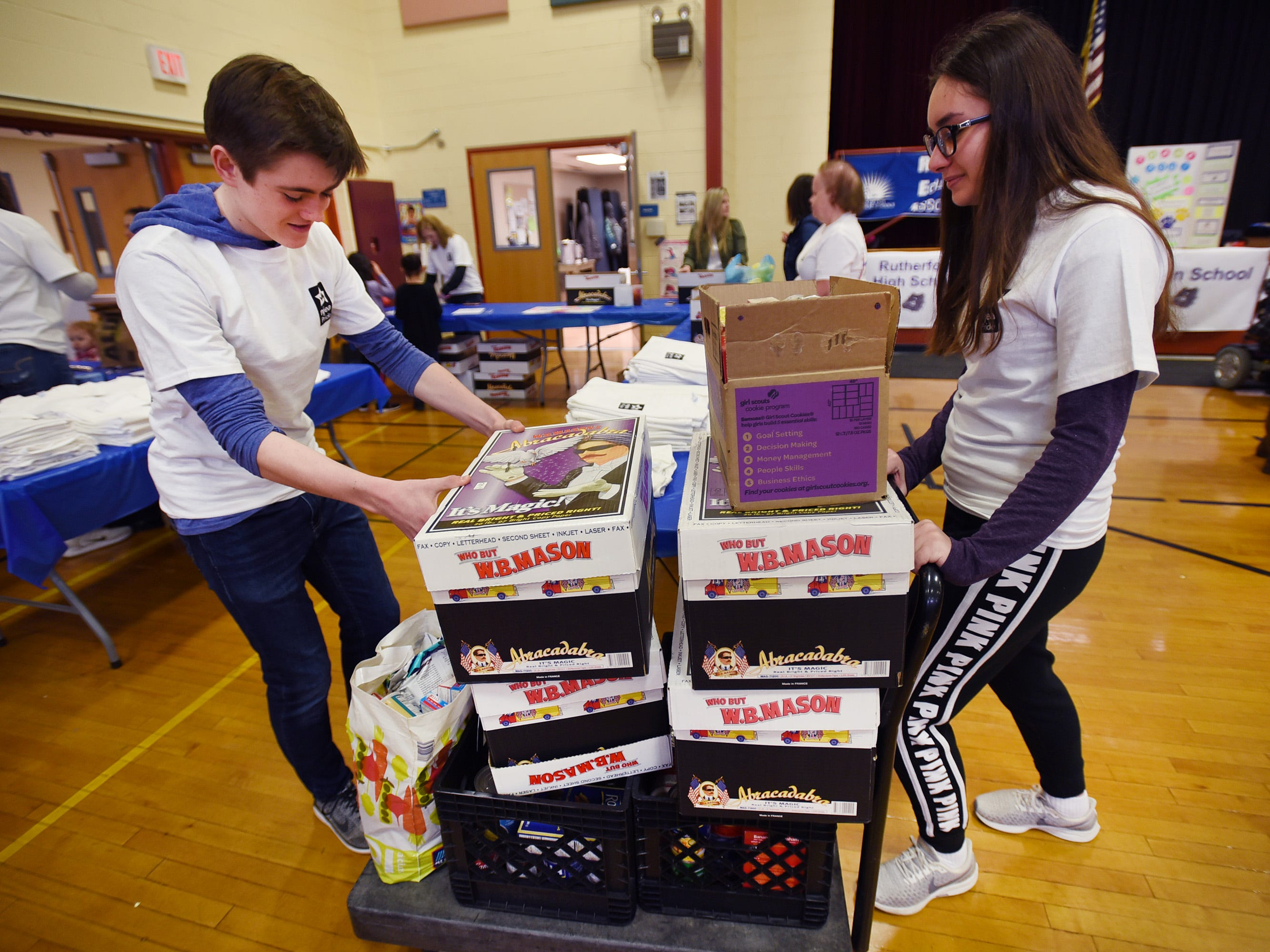 High School volunteer students Shane Kelly and Gabriela Tomczak push a cart full of donated food during the 3rd annual March Madness Food & Fun Day to benefit the Rutherford Food Pantry hosted by the Rutherford Education Association at Washington School in Rutherford on 03/23/2019.