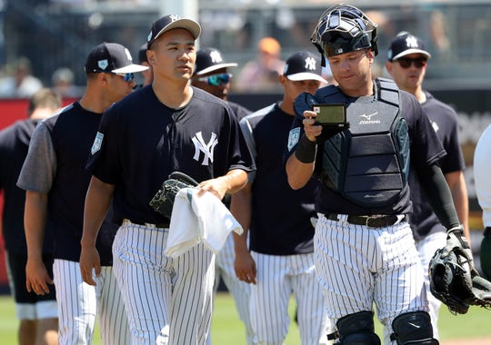 Mar 23, 2019; Tampa, FL, USA;New York Yankees starting pitcher Masahiro Tanaka (19) and New York Yankees catcher Austin Romine (28) walks to the dugout against the Toronto Blue Jays at George M. Steinbrenner Field.