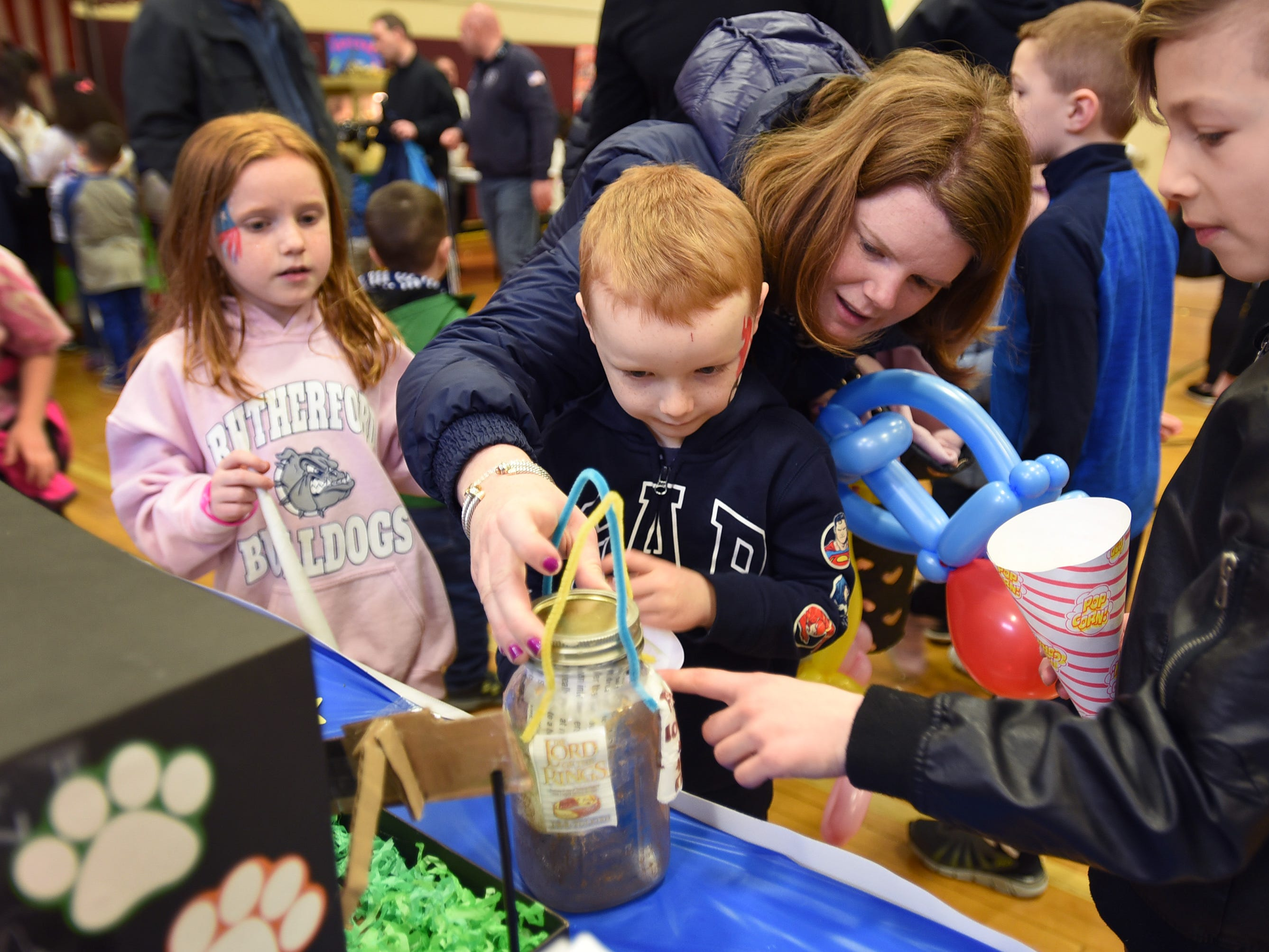 Marykate Parkinson of Rutherford, helps her son James (age 5) to look at a Dream Jar that is displayed during the 3rd annual March Madness Food & Fun Day to benefit the Rutherford Food Pantry hosted by the Rutherford Education Association at Washington School in Rutherford on 03/23/2019.