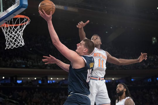 Denver Nuggets center Nikola Jokic (15) goes to the basket past New York Knicks guard Frank Ntilikina (11) during the first half of an NBA basketball game Friday, March 22, 2019, at Madison Square Garden in New York.