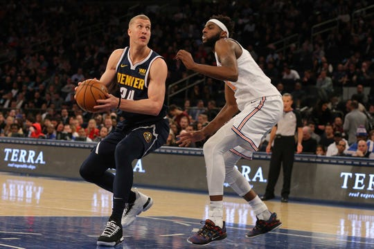 Mar 22, 2019; New York, NY, USA; Denver Nuggets power forward Mason Plumlee (24) controls the ball against New York Knicks center Mitchell Robinson (26) during the second quarter at Madison Square Garden.