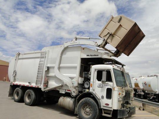A Las Cruces Utilities dump truck empties a dumpster.