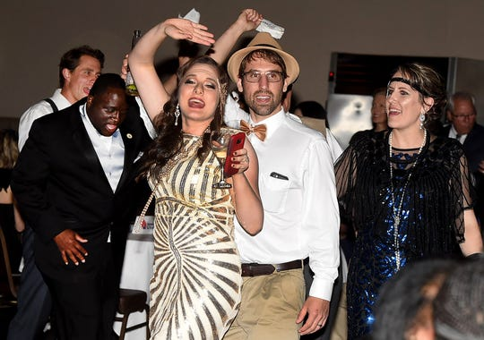 St. Landry Chamber of Commerce President and CEO Raquella Manuel leads a festive group of dancers across the floor at Evangeline Downs on Friday night during the Chamber's Centennial gala.