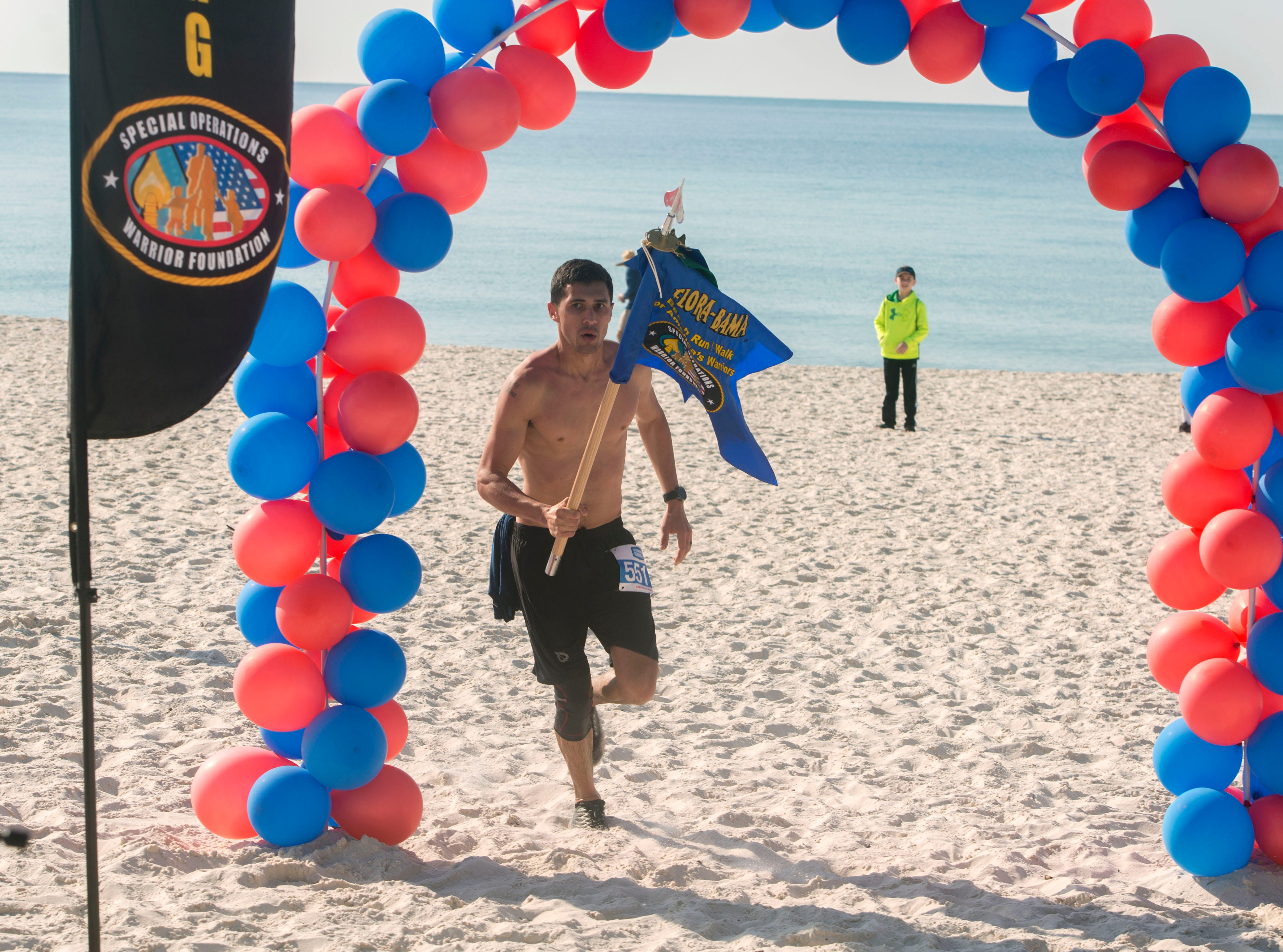 Donald Lach comes across the finish line as the first half marathon finisher Saturday during the 6th annual Flora-Bama Run for America's Warriors half marathon-5k. 100% of the registration fees will go to the Special Operations Warrior Foundation. The Special Operations Warrior Foundation ensures full scholarship grants as well as educational and family counseling to the surviving children of Army, Navy, Air Force and Marine Corps special operations personnel who lose their lives in the line of duty and immediate financial assistance for severely wounded special operations personnel and their families.