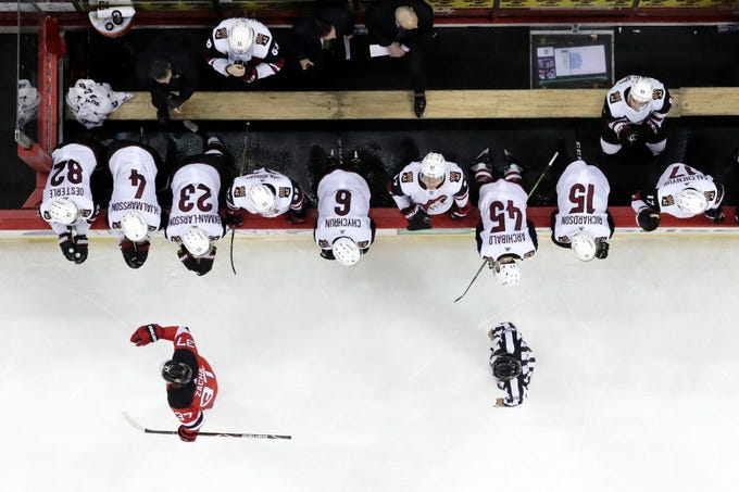 New Jersey Devils center Pavel Zacha, bottom left, of the Czech Republic, skates by the Arizona Coyotes bench after scoring a shootout goal during an NHL hockey game, Saturday, March 23, 2019, in Newark, N.J. The Devils won 2-1 in a shootout.