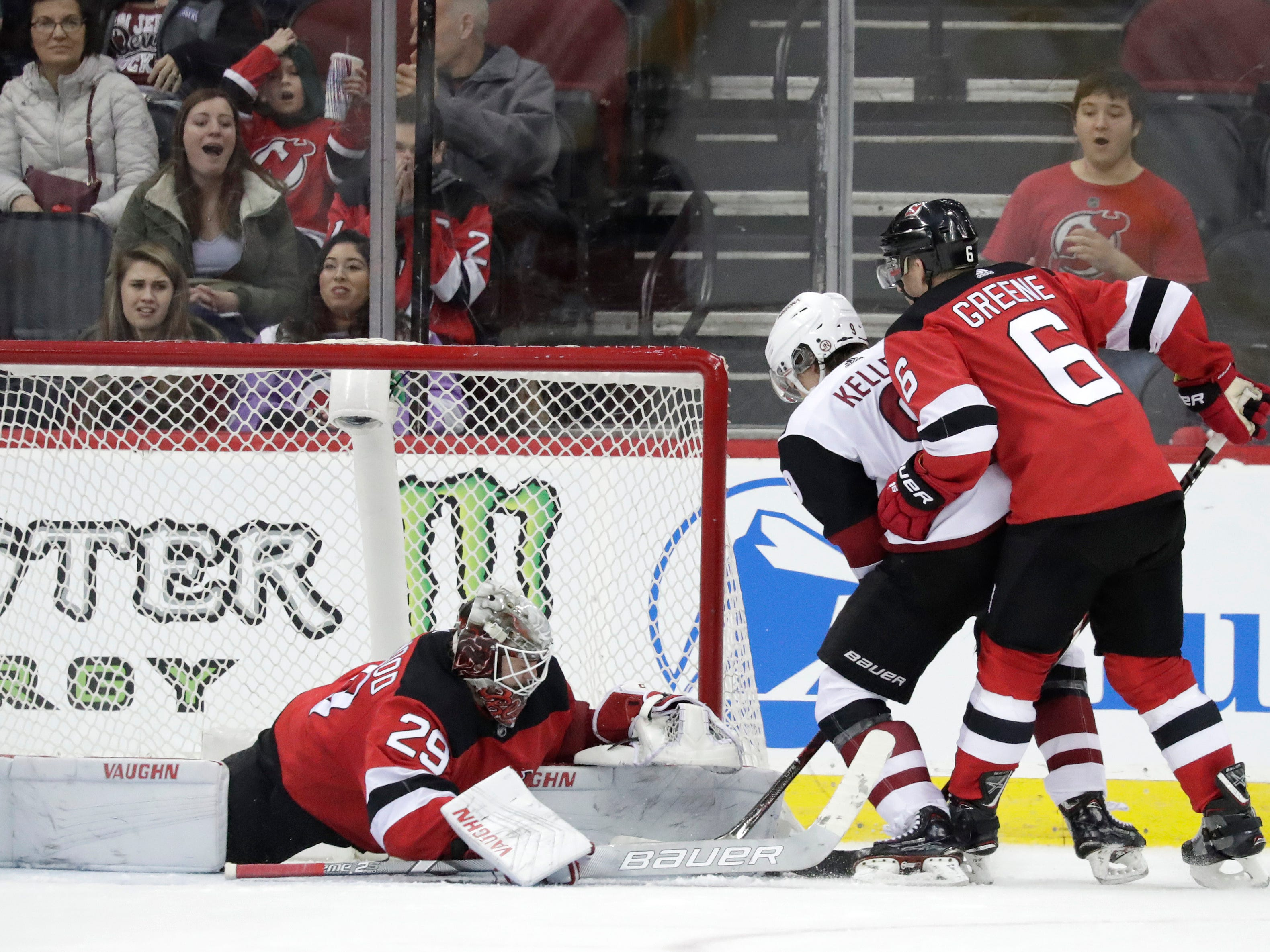 New Jersey Devils goaltender MacKenzie Blackwood (29) makes a save against Arizona Coyotes center Clayton Keller, center, during overtime of an NHL hockey game, Saturday, March 23, 2019, in Newark, N.J. Devils' Andy Greene helps defend on the play. The Devils on 2-1 in a shootout.