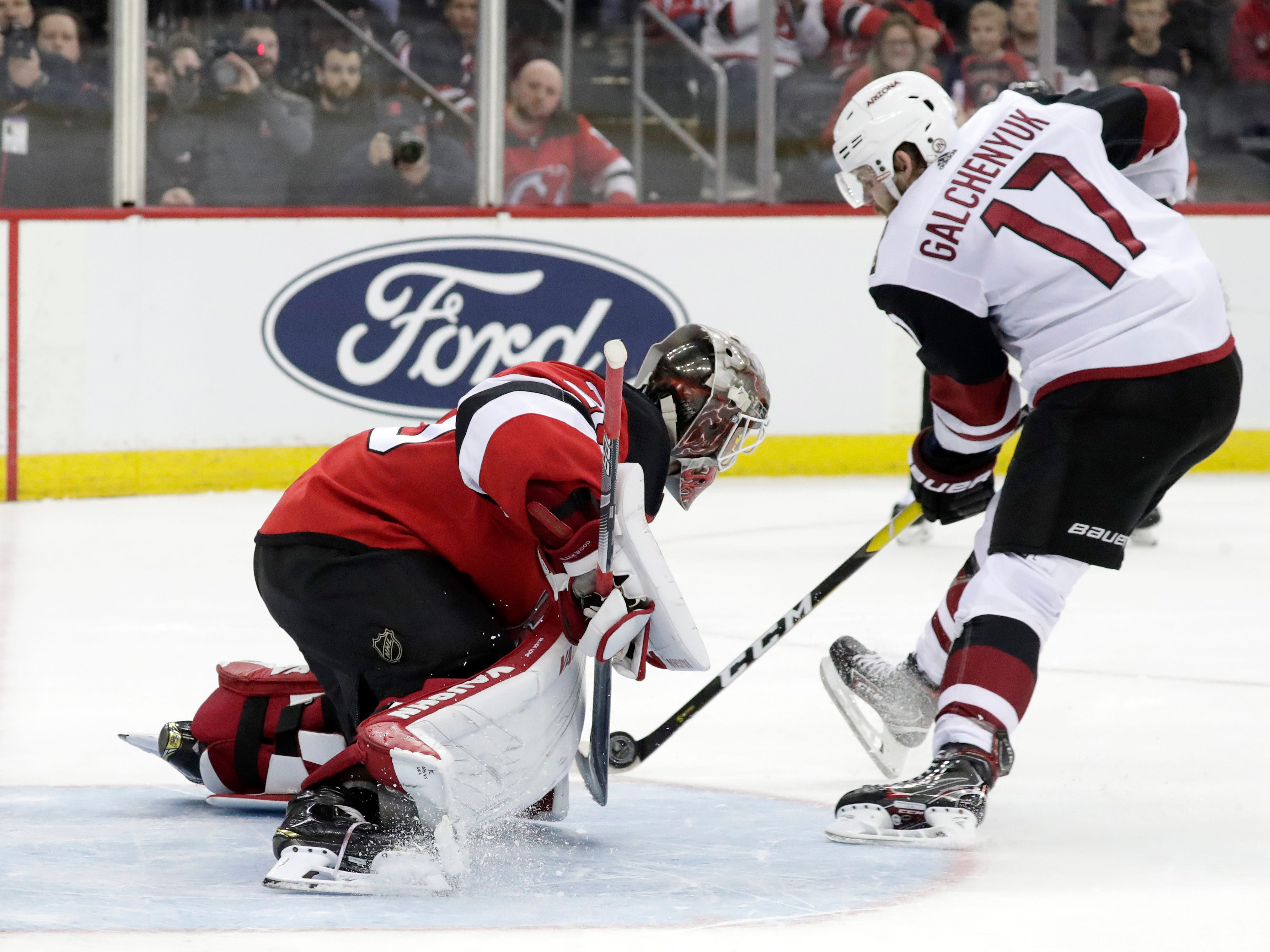 New Jersey Devils goaltender MacKenzie Blackwood, left, blocks a shootout shot by Arizona Coyotes center Alex Galchenyuk (17) during an NHL hockey game, Saturday, March 23, 2019, in Newark, N.J. The Devils on 2-1 in a shootout.