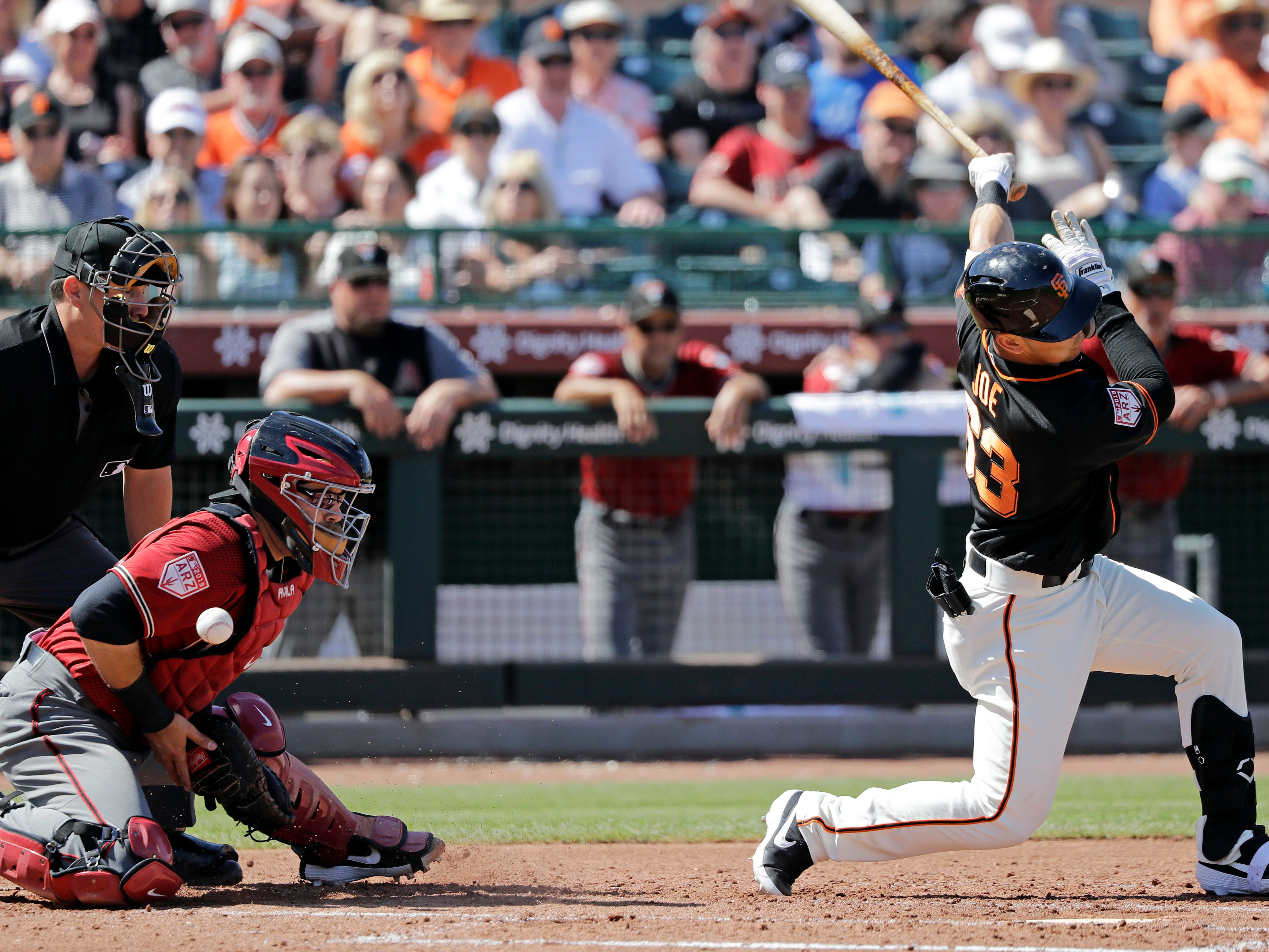 San Francisco Giants' Connor Joe swings and misses for a third strike as the ball gets away from Arizona Diamondbacks catcher Alex Avila with umpire Sean Ryan looking on in the third inning of a spring training baseball game Saturday, March 23, 2019, in Scottsdale, Ariz.