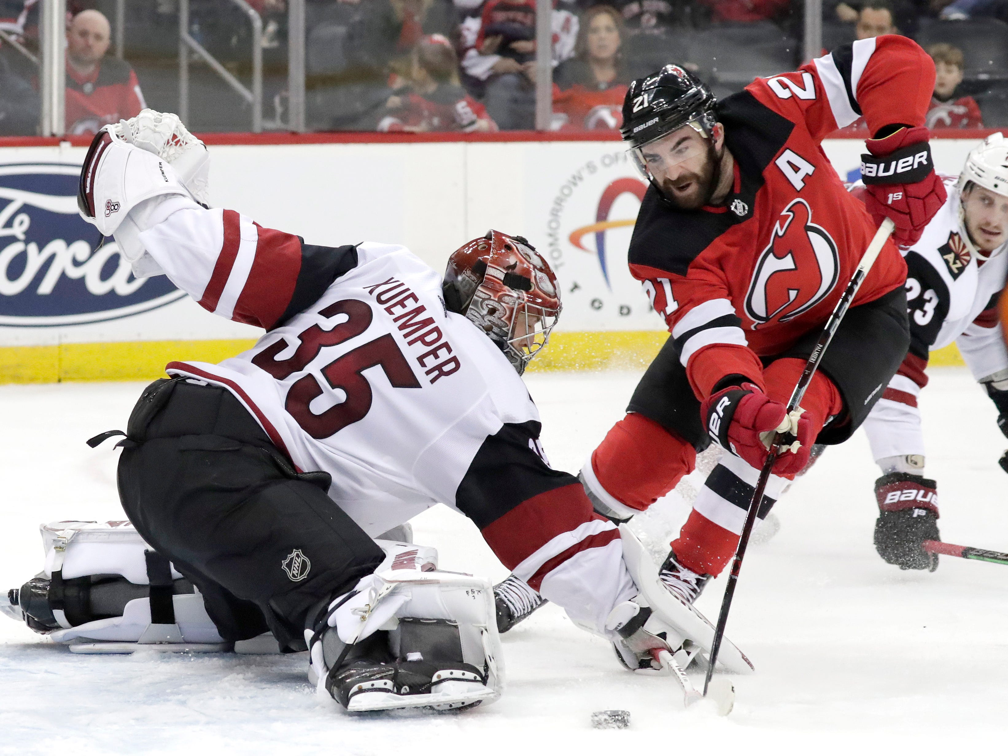 Arizona Coyotes goaltender Darcy Kuemper (35) tries to make a save as New Jersey Devils right wing Kyle Palmieri (21) attacks during the second period of an NHL hockey game, Saturday, March 23, 2019, in Newark, N.J.