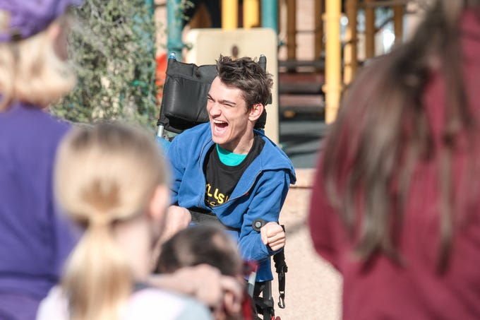 Jake Capstick laughs with friends at The Best Buddies Friendship Walk at Kiwanis Park in Tempe on March 23, 2019.