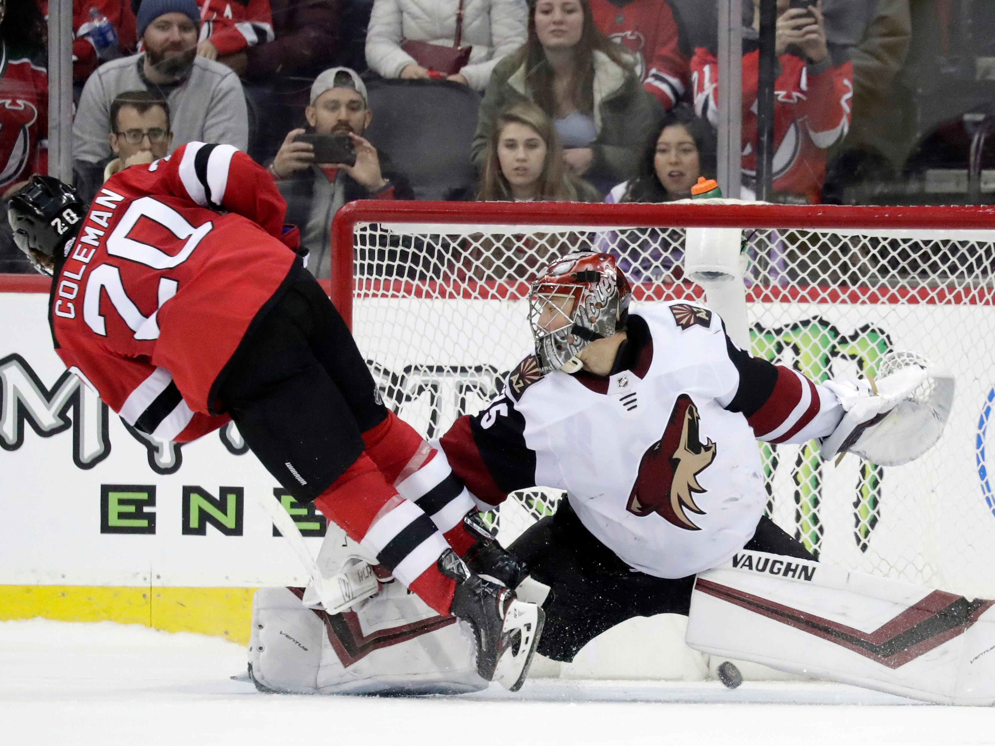 New Jersey Devils center Blake Coleman (20) trips over Arizona Coyotes goaltender Darcy Kuemper (35) while scoring during a shootout in an NHL hockey game, Saturday, March 23, 2019, in Newark, N.J. The Devils on 2-1 in a shootout.