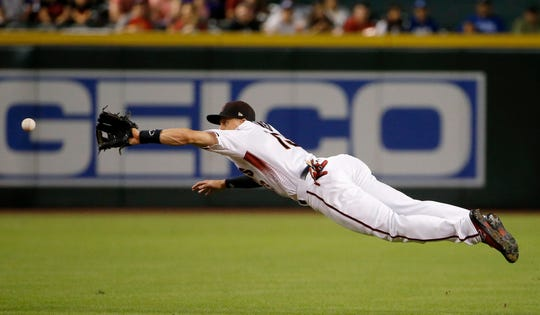 Arizona Diamondbacks shortstop Nick Ahmed reaches out to field a grounder hit by Los Angeles Dodgers' Max Muncy, but is unable to get the throw to first base in time, during the first inning of a baseball game Wednesday, Sept. 26, 2018, in Phoenix. (AP Photo/Ross D. Franklin)