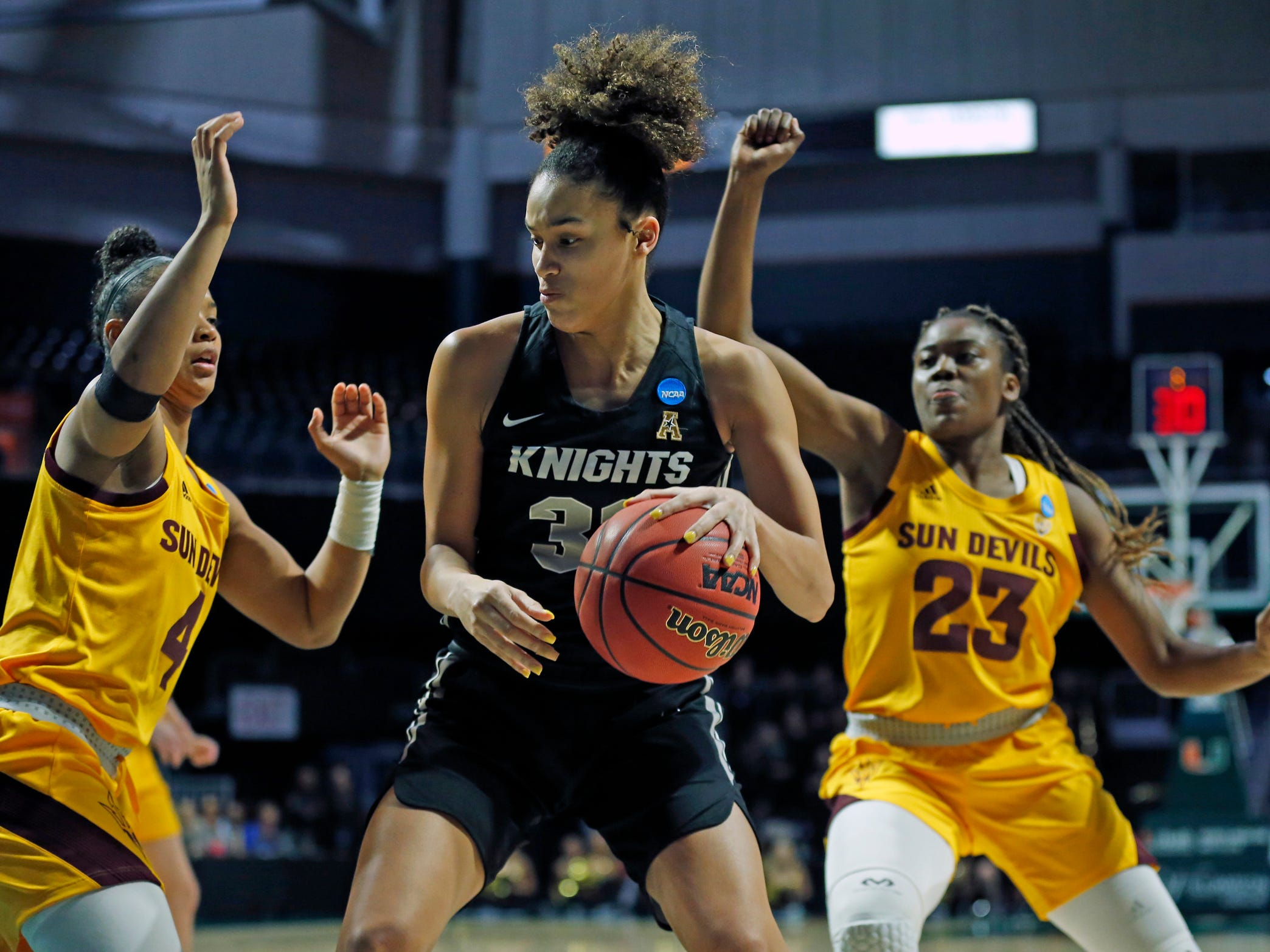UCF guard Diamond Battles (3) drives the ball in between Arizona State guard Iris Mbulito (23) and Arizona State guard Kiara Russell (4), during a first round women's college basketball game in the NCAA Tournament in Coral Gables, Fla., Friday, March 22, 2019. (Al Diaz/Miami Herald via AP)