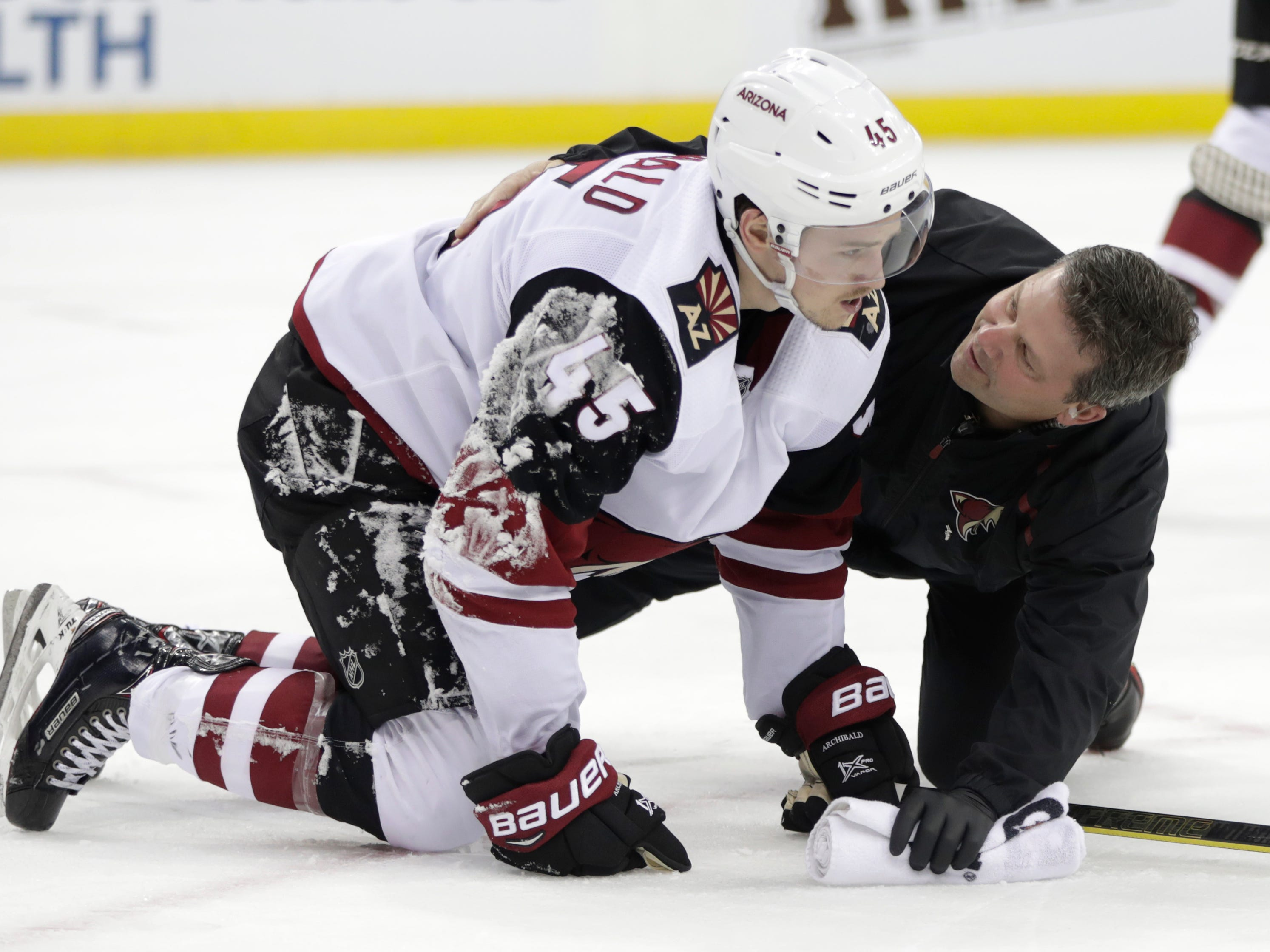 A trainer talks to Arizona Coyotes right wing Josh Archibald (45) during the second period of an NHL hockey game against the New Jersey Devils, Saturday, March 23, 2019, in Newark, N.J.