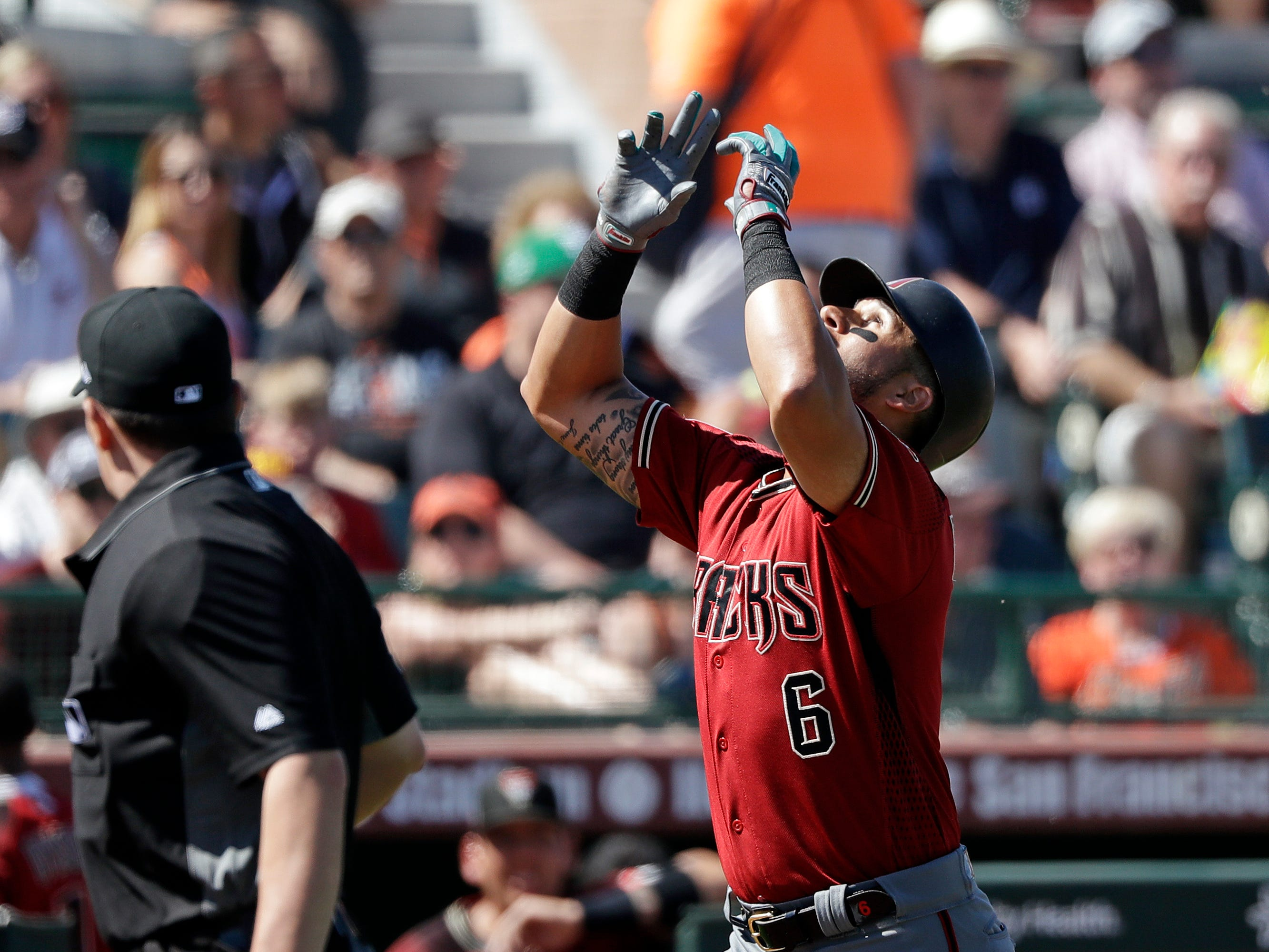 Arizona Diamondbacks' David Peralta gestures skyward as he heads home on his solo home run against the San Francisco Giants in the third inning of a spring training baseball game Saturday, March 23, 2019, in Scottsdale, Ariz.