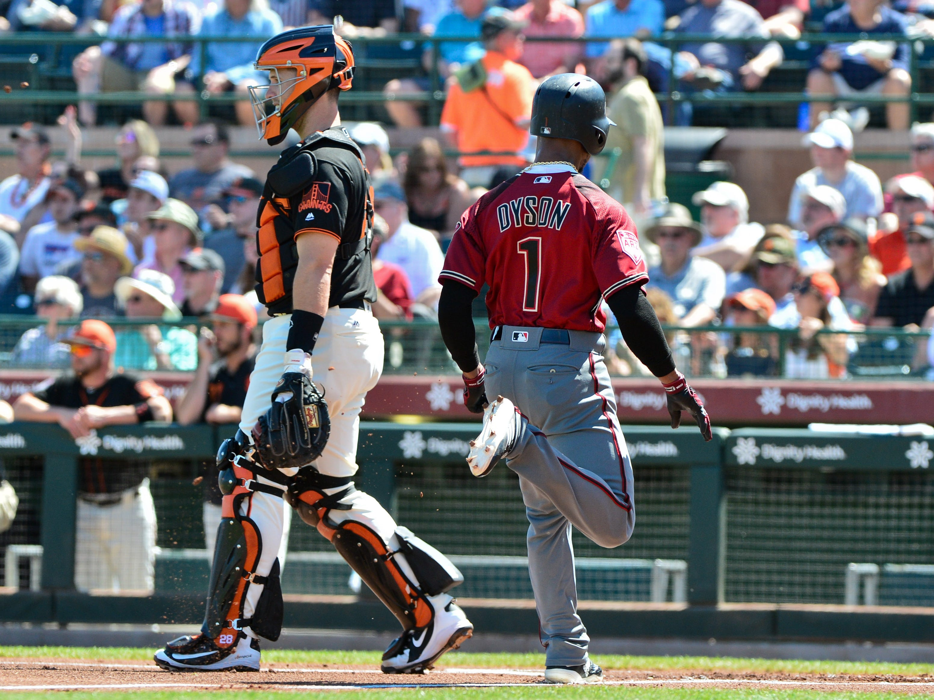 Mar 23, 2019; Scottsdale, AZ, USA; Arizona Diamondbacks center fielder Jarrod Dyson (1) scores a run behind San Francisco Giants catcher Buster Posey (28) during the first inning at Scottsdale Stadium.