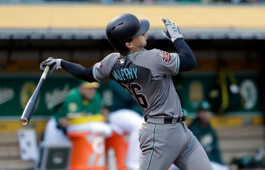 Arizona Diamondbacks' John Ryan Murphy follows through on a two-run double during the third inning of the team's baseball game against the Oakland Athletics on Friday, May 25, 2018, in Oakland, Calif. (AP Photo/Marcio Jose Sanchez)