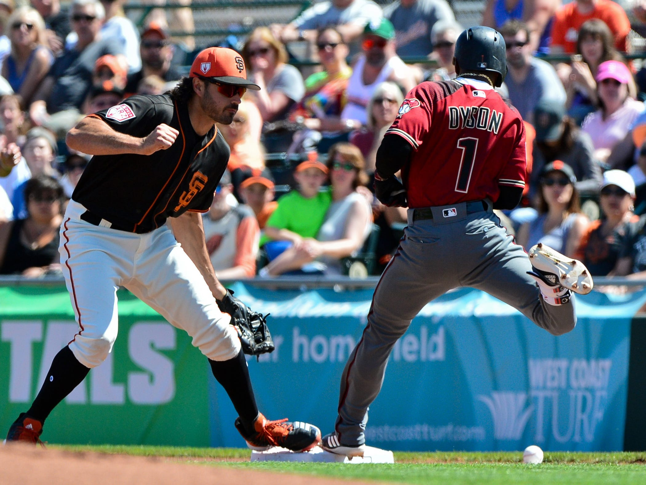 Mar 23, 2019; Scottsdale, AZ, USA; Arizona Diamondbacks center fielder Jarrod Dyson (1) touches first base as San Francisco Giants catcher Aramis Garcia (16) misses the ball during the first inning at Scottsdale Stadium.