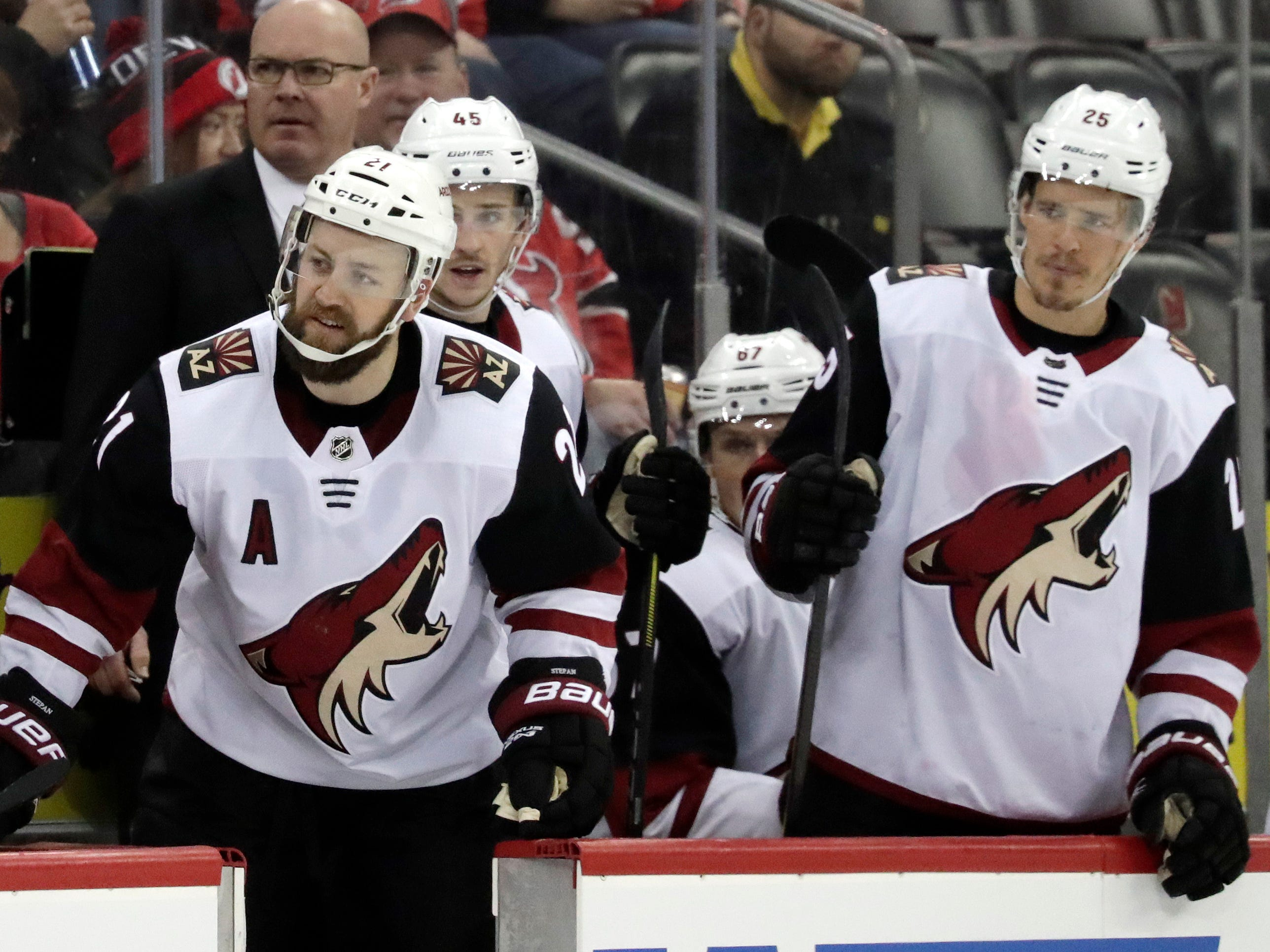 Arizona Coyotes center Derek Stepan, left, looks over at the New Jersey Devils bench during the third period of an NHL hockey game, Saturday, March 23, 2019, in Newark, N.J. The Devils on 2-1 in a shootout.