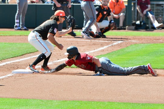 Mar 23, 2019: Arizona Diamondbacks shortstop Nick Ahmed (13) tags up as San Francisco Giants catcher Aramis Garcia (16) catches the ball during the fourth inning at Scottsdale Stadium.