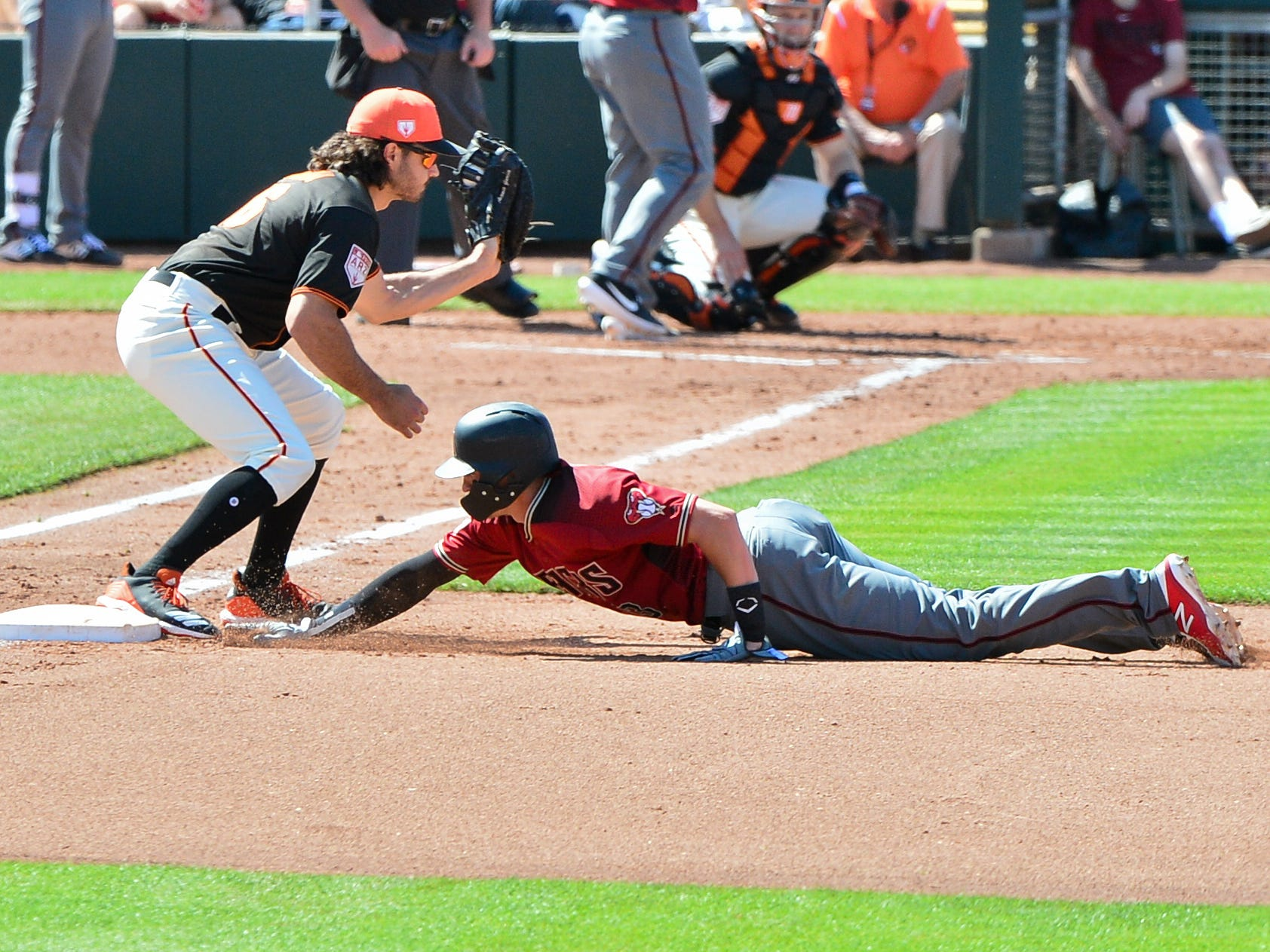 Mar 23, 2019; Scottsdale, AZ, USA; Arizona Diamondbacks shortstop Nick Ahmed (13) tags up as San Francisco Giants catcher Aramis Garcia (16) catches the ball during the fourth inning at Scottsdale Stadium.