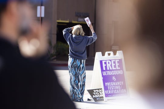 Denise Harkison directs people to the rally outside Papago Medical Park, a clinic that performs abortions, on March 23, 2019.