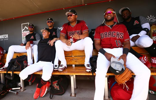 Diamondbacks Yoan Lopez, Yasmany Tomas and Socrates Brito hang out in the dugout before a spring training game.