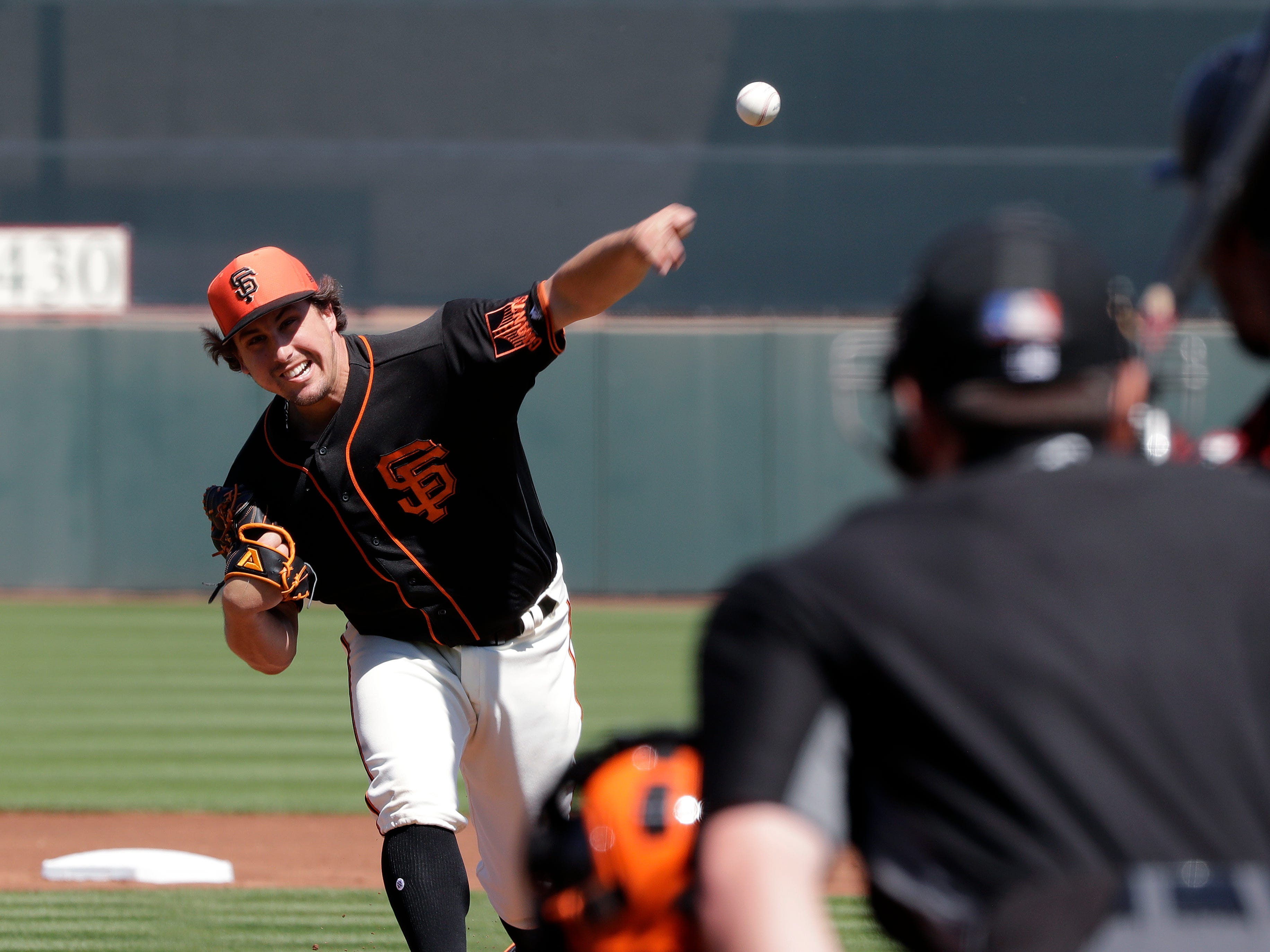 San Francisco Giants starting pitcher Derek Holland, left, throws against Arizona Diamondbacks' Jarrod Dyson in the first inning of a spring training baseball game Saturday, March 23, 2019, in Scottsdale, Ariz.
