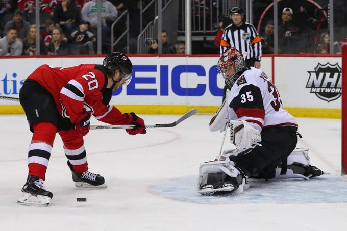 Coyotes goaltender Darcy Kuemper (35) makes a save in front of Devils center Blake Coleman (20) during the second period of a game at Prudential Center.