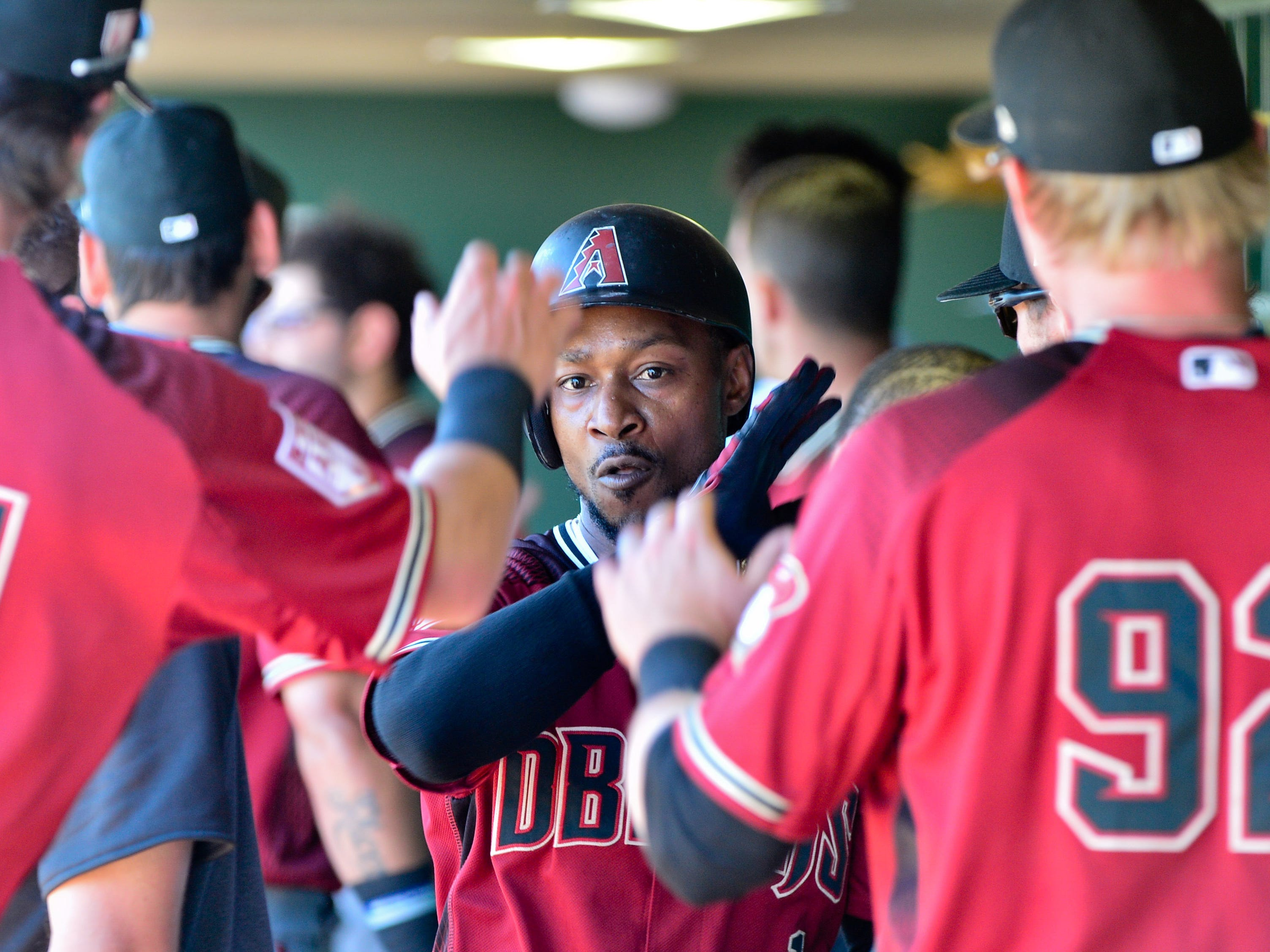 Mar 23, 2019; Scottsdale, AZ, USA; Arizona Diamondbacks center fielder Jarrod Dyson (1) celebrates with teammates during the first inning after scoring a run against the San Francisco Giants at Scottsdale Stadium.