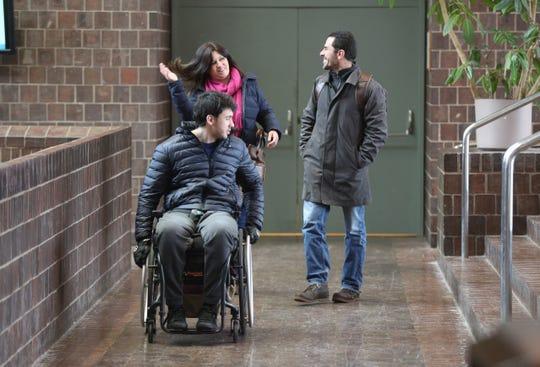 Giuliano Agostinho de Castro with his parents, Marcia Cristina Esteves Agostinho and  Gilberto Teixeira de Castro, make their way around Wilson Commons on the University of Rochester campus.