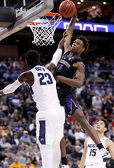 Washington's Nahziah Carter (11) tries to dunk over Utah State's Neemias Queta (23) in the second half during a first round men's college basketball game in the NCAA Tournament in Columbus, Ohio, March 22, 2019.