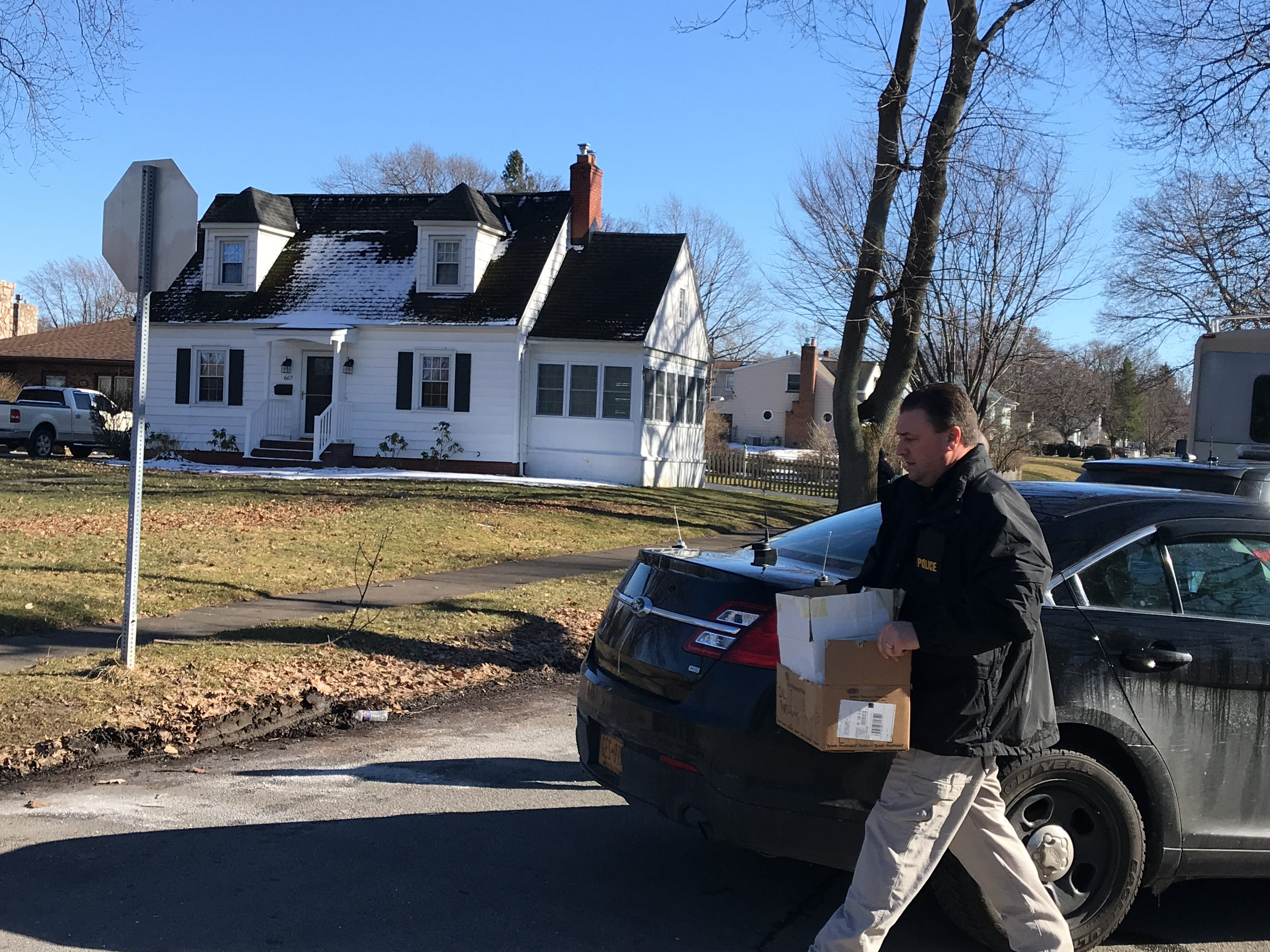 A police officer carries away items from the scene of a suspicious death on Lakeshore Boulevard.