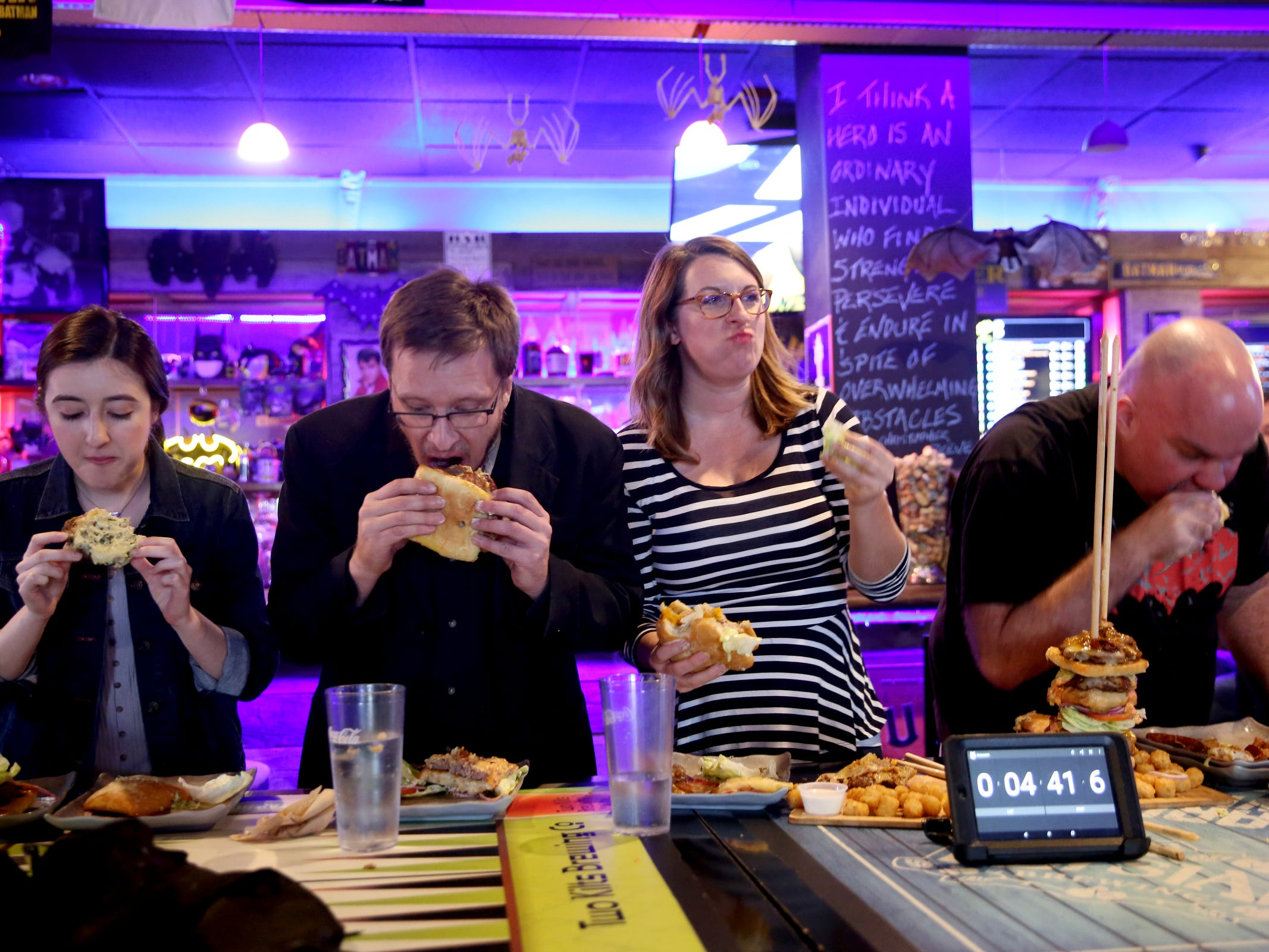 "Statesman Journal reporters, from left, Virginia Barreda, Ben Botkin and Emily Teel go up against competitive eater ""Max Carnage"" during a Statesman Journal eating challenge to finish the Dark Knight Burger, consisting of six top-selling burgers, at Heroes Tap House in Salem on March 22, 2019. The Statesman Journal crew finished the stack in 35 minutes."